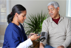 caregiver checking the blood pressure of her patient